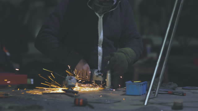 Nicht erkennbare Stahlarbeiter mit kreisförmigen sah zum Schleifen von Metall in einer Werkstatt.