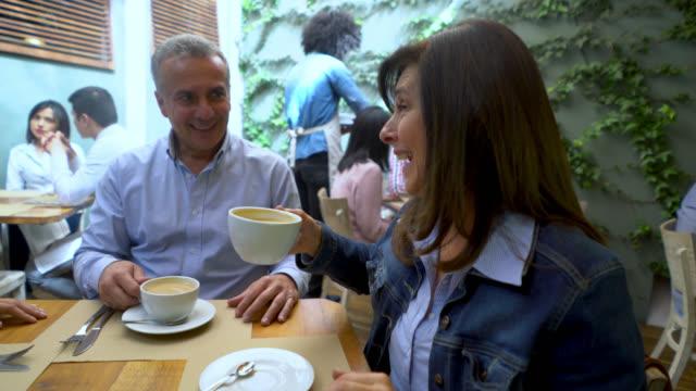 Onherkenbaar ober serveren van koffie aan een groep van mensen en vrouwelijke klant probeert het