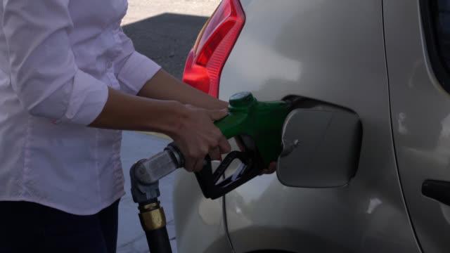 Onherkenbaar vrouw openen van de kraan van de brandstof pomp haar auto