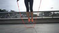 Unrecognizable woman training outdoors jumping rope