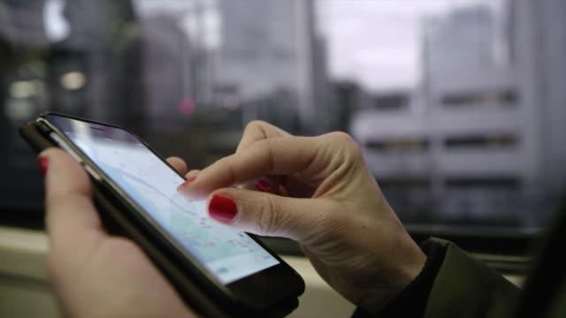CU oigenkännlig kvinna använder sin smartphone på ett tåg