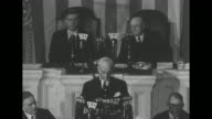 VO unseen audience applauds as standing on rostrum US Secretary of State Cordell Hull reports to Congress on the Third Moscow Conference from which...