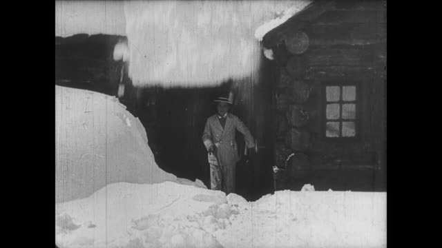Unsuspecting Buster Keaton is doused in roof snow upon exiting winter cabin