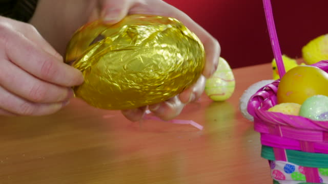 Unwrapping chocolate Easter egg