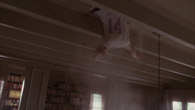Up angle of ceiling with wooden beams running across. walls with decorative molding. bookcases. middle or upper class. woman falls through and hangs or dangles from ceiling. desperately trying not to fall. bare legs. stunts.