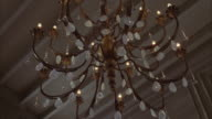 Up angle of chandelier hanging from ceiling with crystals. light bulbs and fixture.