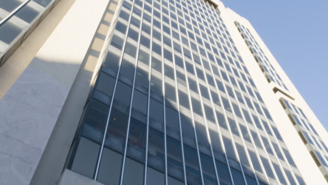 up angle of multi-story office building. sign reads adam clayton powell jr state offices. government buildings.