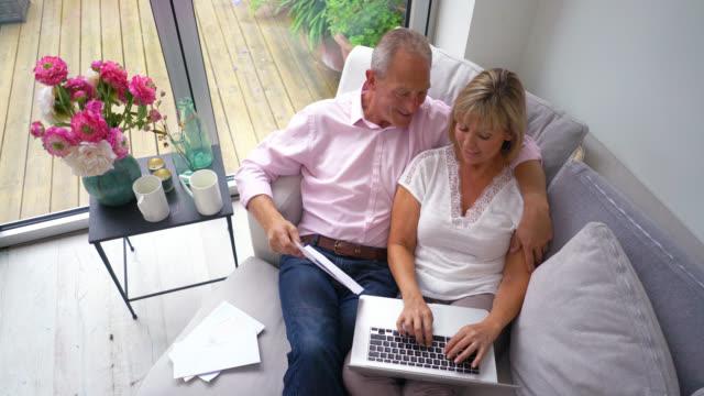 Övre bild av paret på soffan och betala sina räkningar online