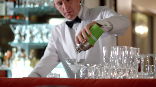 MS upscale bartender shakes cocktail shaker in his hand and pours drink into martini glass sitting on bar counter