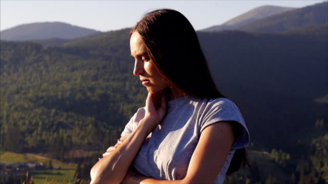 Upset female standing at sunset in mountains