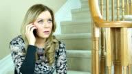 Upset woman talking on mobile phone