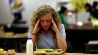 Upset young teenager in school cafeteria