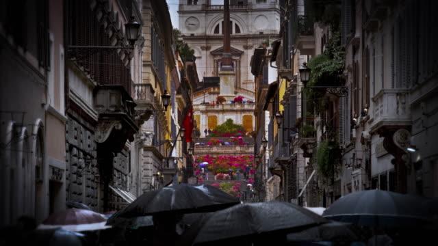 Upward slow motion tilt from street to Via Dei Condotti