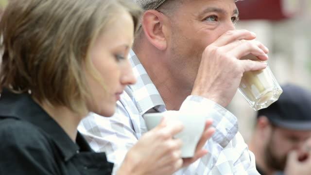 Urban couple drinking coffee outdoors