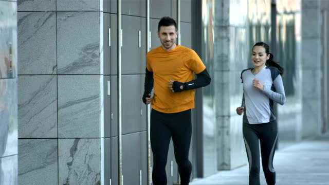HD SLOW MOTION: Urban Couple Jogging In The Morning