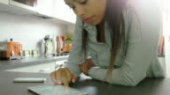 Using digital tablet and phone. Young woman, kitchen.