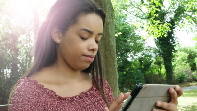 Using digital tablet, outdoors. Young woman.