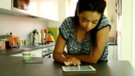 Using digital tablet. Young woman, kitchen.
