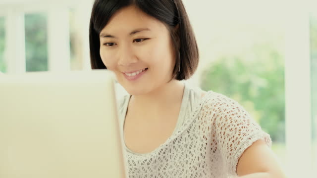 Using laptop, Asian woman. Dolly shot.