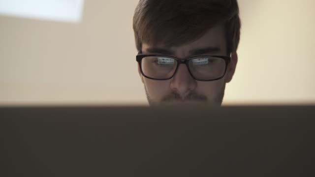 Met behulp van laptop, scherm reflectie in brillenglazen. Groothoek schot.