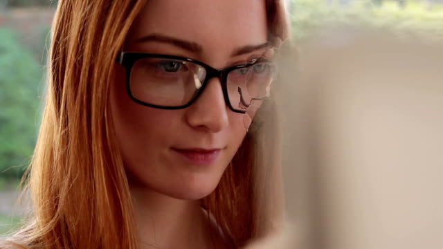 Using laptop, young woman wearing glasses.