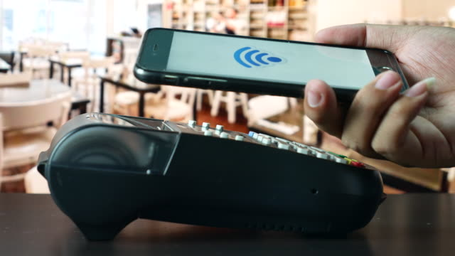 Using mobile paying by contactless payment with phone in cafe, NFC Payment