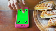 Using smart Phone Which Laying on Wooden Table at restaurant