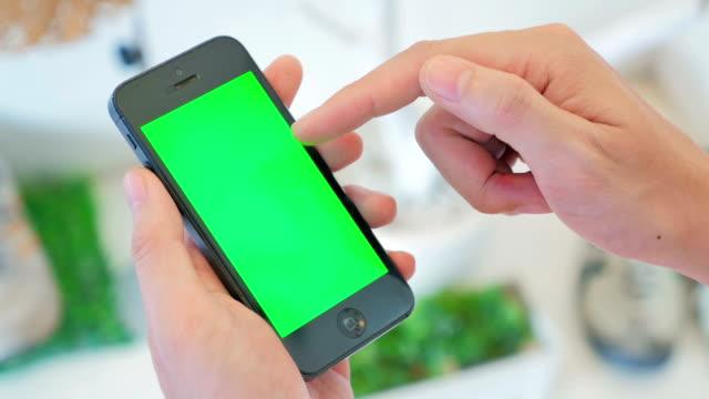 Utilizzando uno smartphone, schermo verde, primo piano