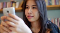 Using smartphone, young woman at Restaurant