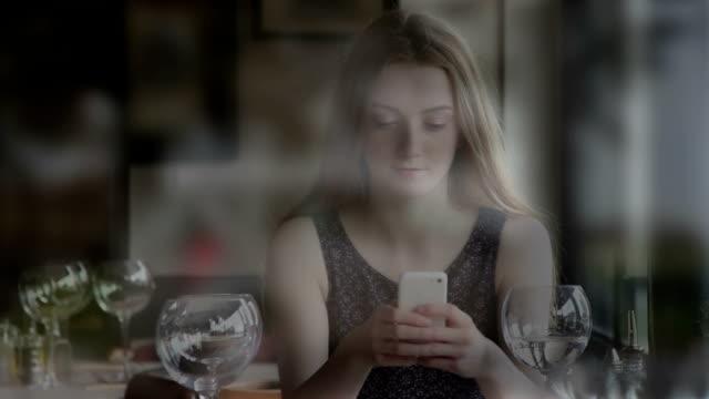 Utilizzando uno smartphone, giovane donna in un ristorante, vista attraverso una finestra.