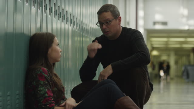 USA, Utah, Alpine, Mature man talking with teenage girl (14-15) at school