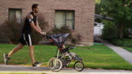 USA, Utah, Provo, Father jogging with son (6-11 months) in stroller