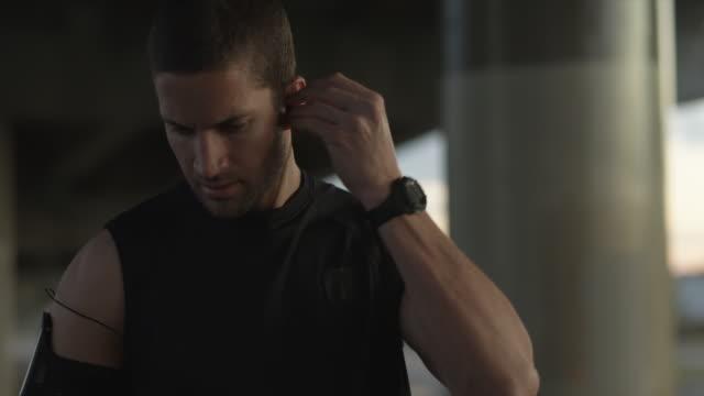 USA, Utah, Provo, Young man preparing to jog by putting headphones on
