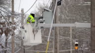 Utlility worker in cherry picker fixing powerlines after snowstorm