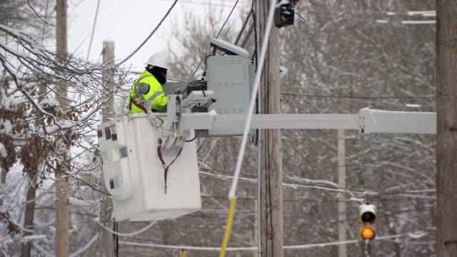 Utlility worker in cherry picker fixing powerlines after snowstorm