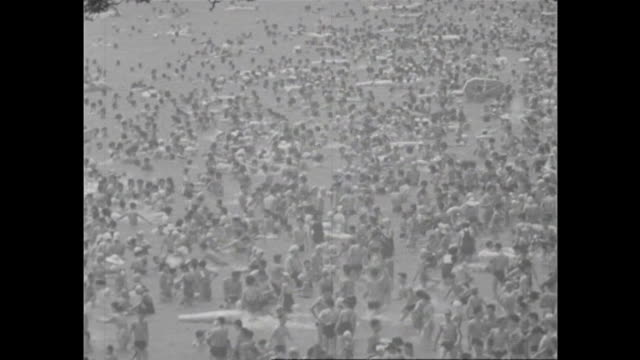 Vacationers enjoy swimming on a crowded beach resort near Enoshima in Kanagawa / During the highgrowth period in Japan