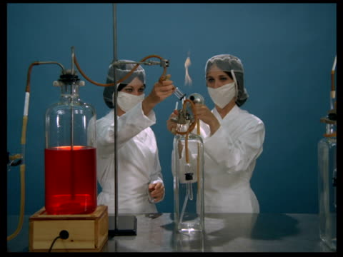 Vaccine production CU of red liquid in bottle PAN to gas burner ZOOM OUT to include two female technicians filling bottles with syphon / PAN along...