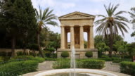 Valetta, view a fountain in the lower Barakka gardens, with yje Neo-Classical temple in the background