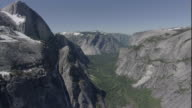 A valley lies far below the towering mountain peaks of Yosemite National Park. Available in HD.