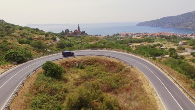 AERIAL Van driving on road leading to village of Komiza