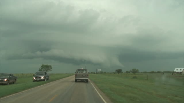 Van driving towards dramatic looking shelf cloud or wall cloud under severe supercell thunderstorm, USA.