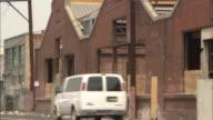 A van passes abandoned warehouses.