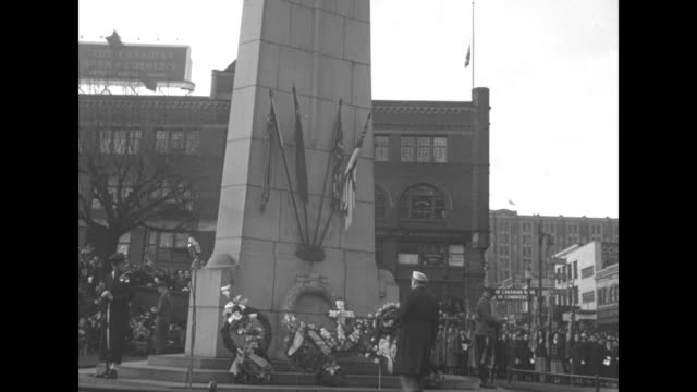Vancouver Canada high angle Victory Square Cenotaph monument / bugler soldiers and crowd / VS Boer War Monument Melbourne Australia man lays a wreath...