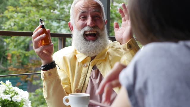 Vaping - Brief. Bearded gray-haired happy man talking with a woman and holding an electronic cigarette in a cafe