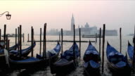 WS Vapporettoes moving past moored gondolas at sunset, San Giorgio Maggiore in background, Venice, Veneto, Italy