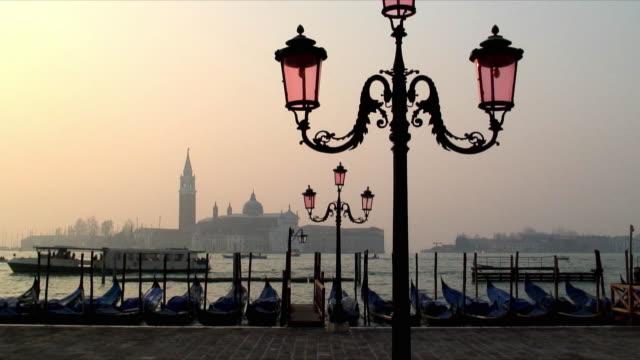 WS Vapporettoes moving past moored gondolas at sunset, San Giorgio Maggiore in background, Venice, Veneto, Italy