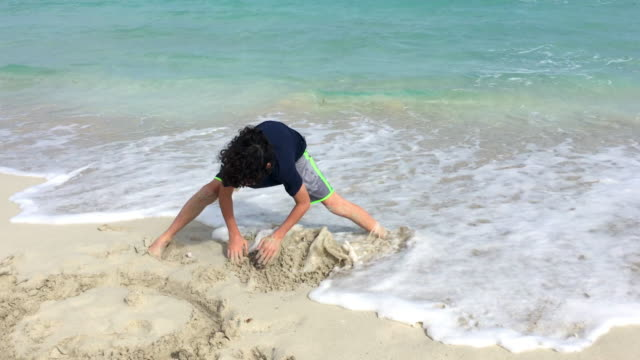 Varadero, Cuba: Young child boy plays in the white sand during a bad weather day when swimming is not allowed in the tropical beach