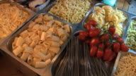 A variety of homemade pasta is displayed in baskets.