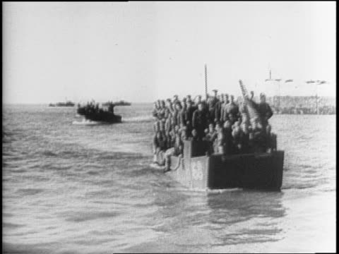 Various angles of landing boats carrying Canadian Commandos landing on beach in France / tank driving off of landing boat / soldiers running across...