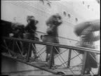 Various angles of soldiers walking down ship's gangplank / soldiers checking in at desk / soldiers gathering in port / montage of soldiers receiving...